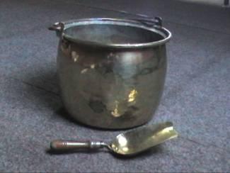 Oude gele koperketel met handvat en kolenschop in geel koper